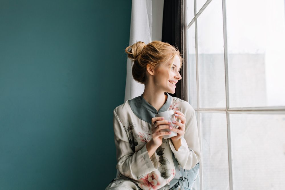 Portrait of young woman with blonde hair drinking coffee or tea next to big window, smiling, enjoying happy morning at home. Turquoise wall on background. Wearing silk pajamas in flowers.