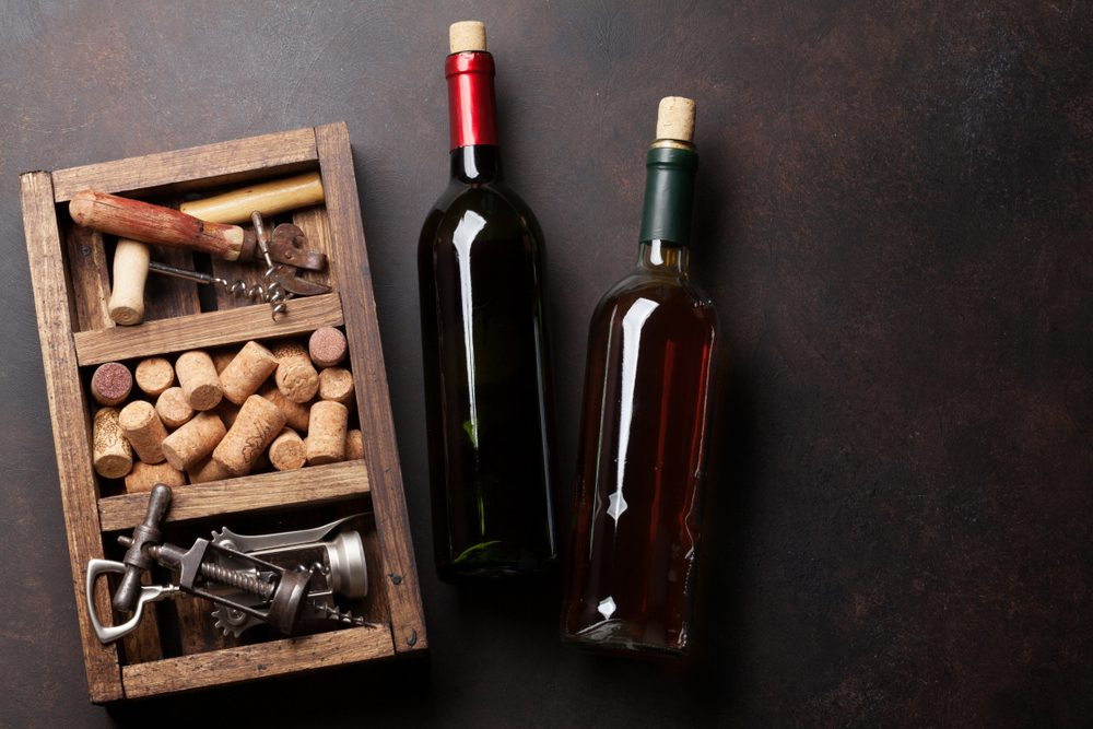 Wine bottles, corkscrew and corks in wooden box. Top view with space for your text