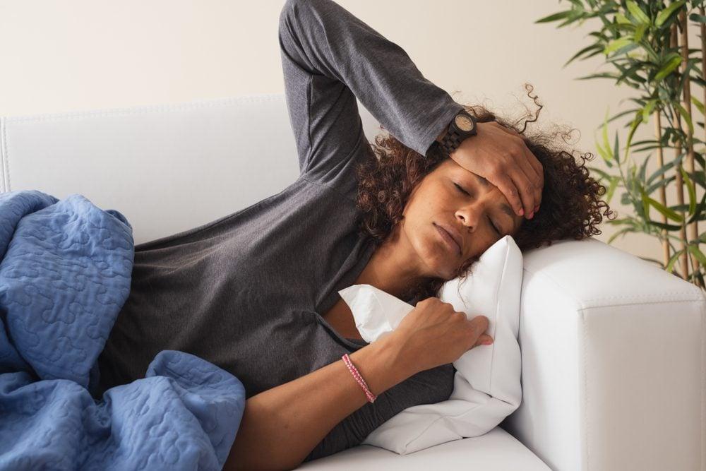 Sick black woman feeling her forehead hot