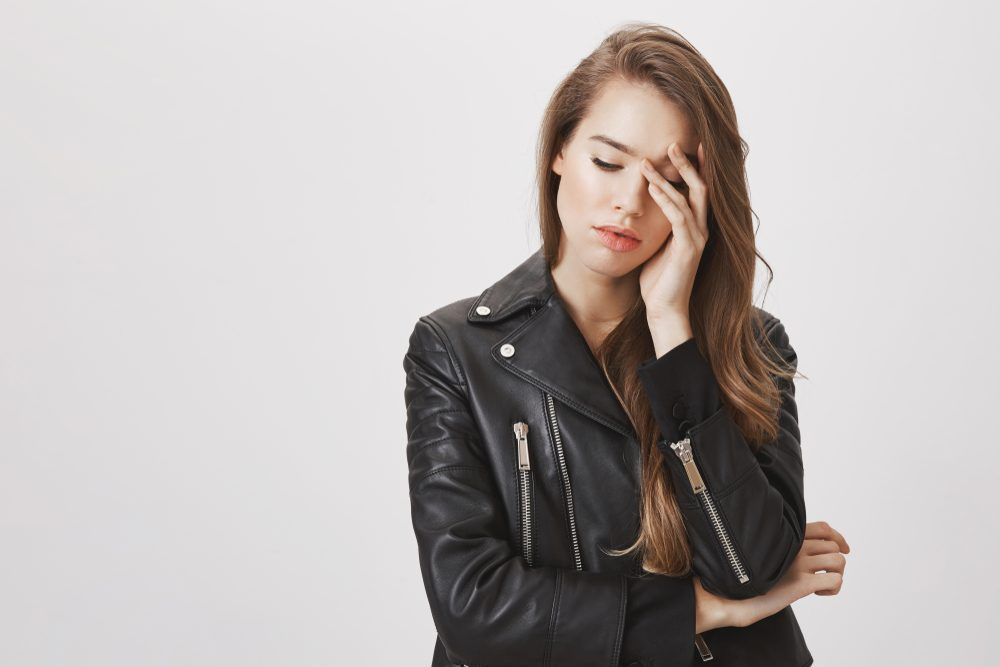 Studio shot of gloomy feminine urban woman in leather jacket looking down and touching forehead with hands, feeling miserable or exhausted, having headache from stress, standing over gray background