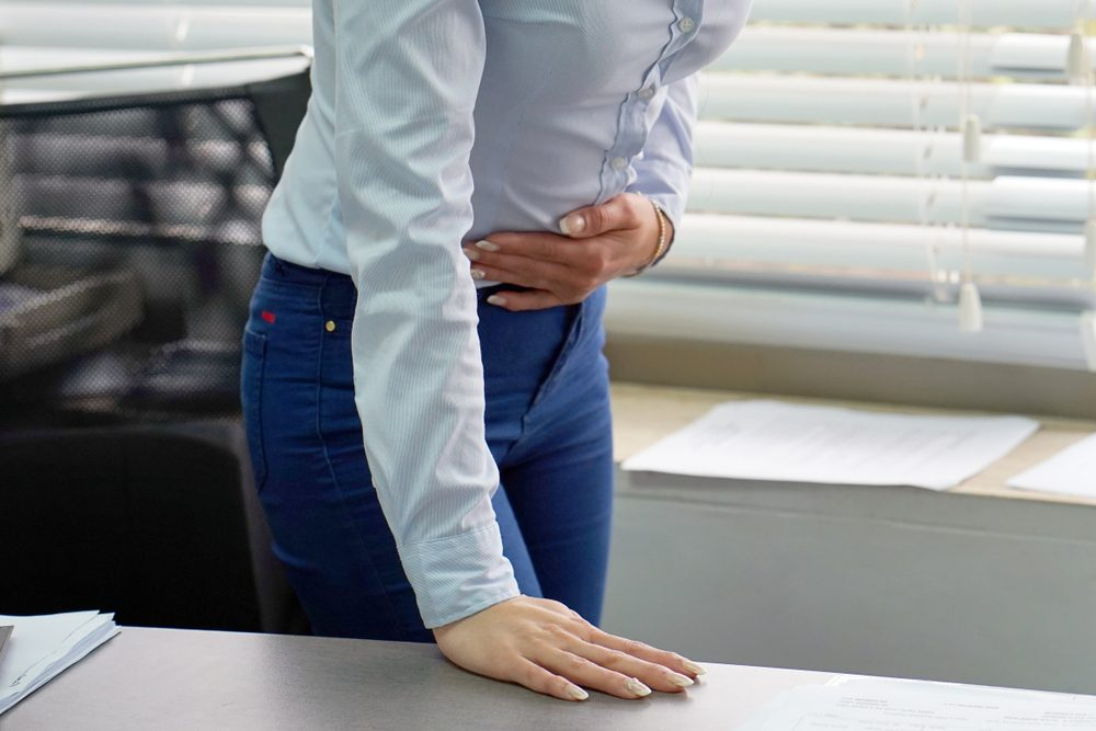 Close-up office worker Woman having painful stomachache. Chronic gastritis. Body And Health Care Concept.
