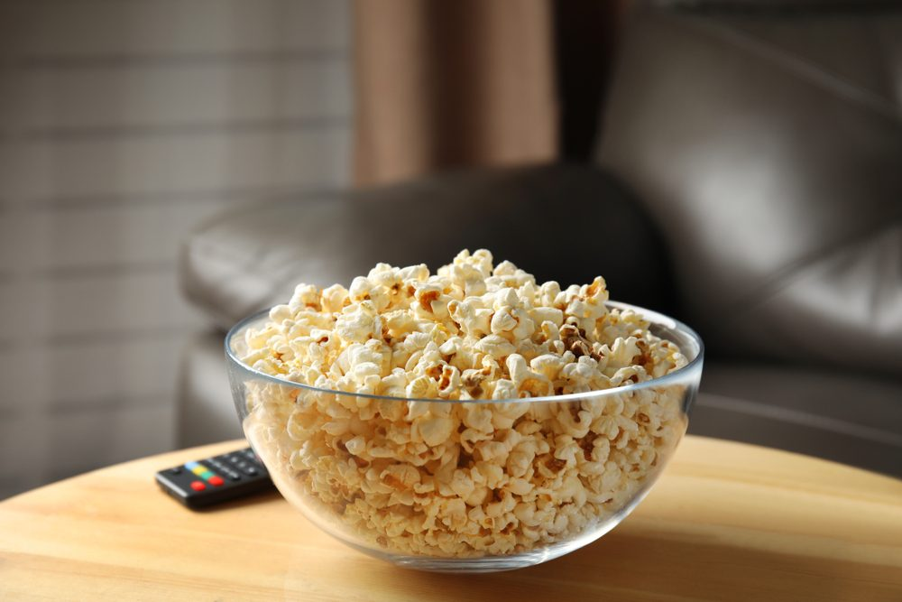 Bowl of popcorn and TV remote on table against blurred background. Watching cinema