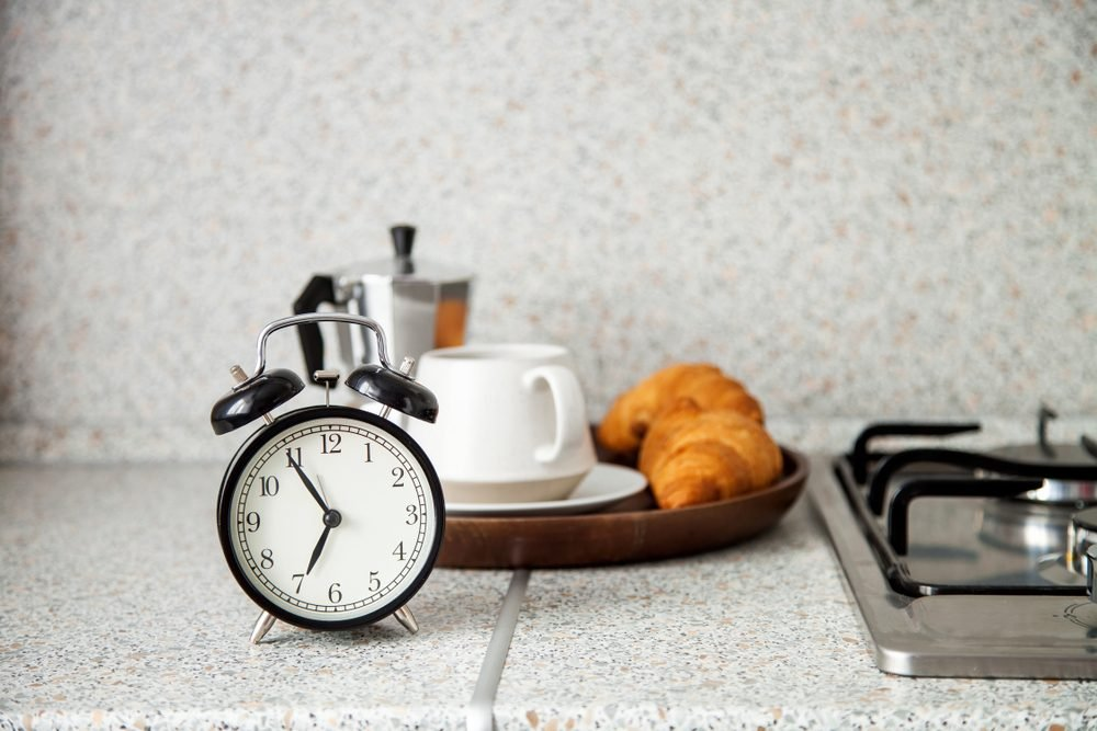 Breakfast concept. The alarm clock, coffee, croissant in an interior of kitchen. Selective focus