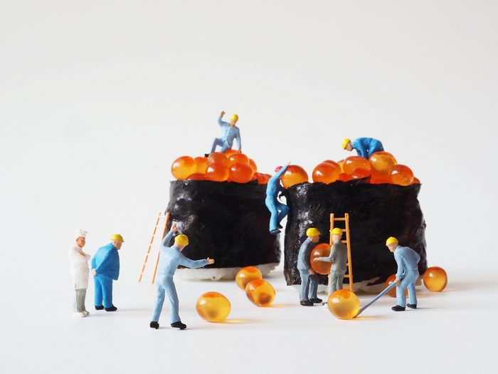 Close up miniature people many of worker man making a maki roll over white background,team work concept.