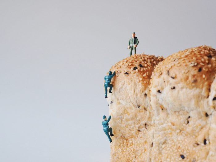 Miniature people Hiking trail on mountain bread.