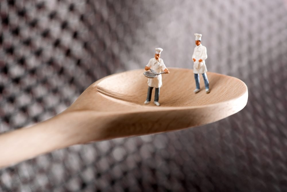 Two miniature figures of chefs or cooks on a wooden spoon over a textured metal background in a concept of catering and food preparation