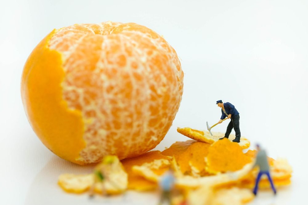 Miniature people: Worker working on the orange peel to clean it using for creativity , artwork business concept.