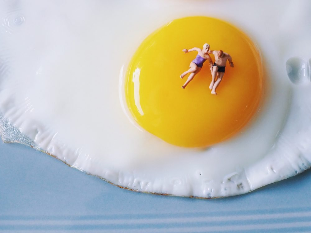 Close up couple lover miniature people laying on yolk of fire egg.