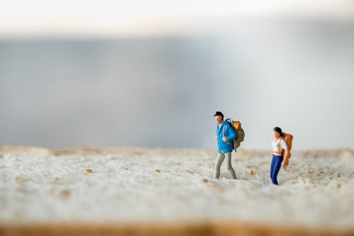 Travel and food concept. Two traveler miniature figures walking on whole wheat bread with copyspace.
