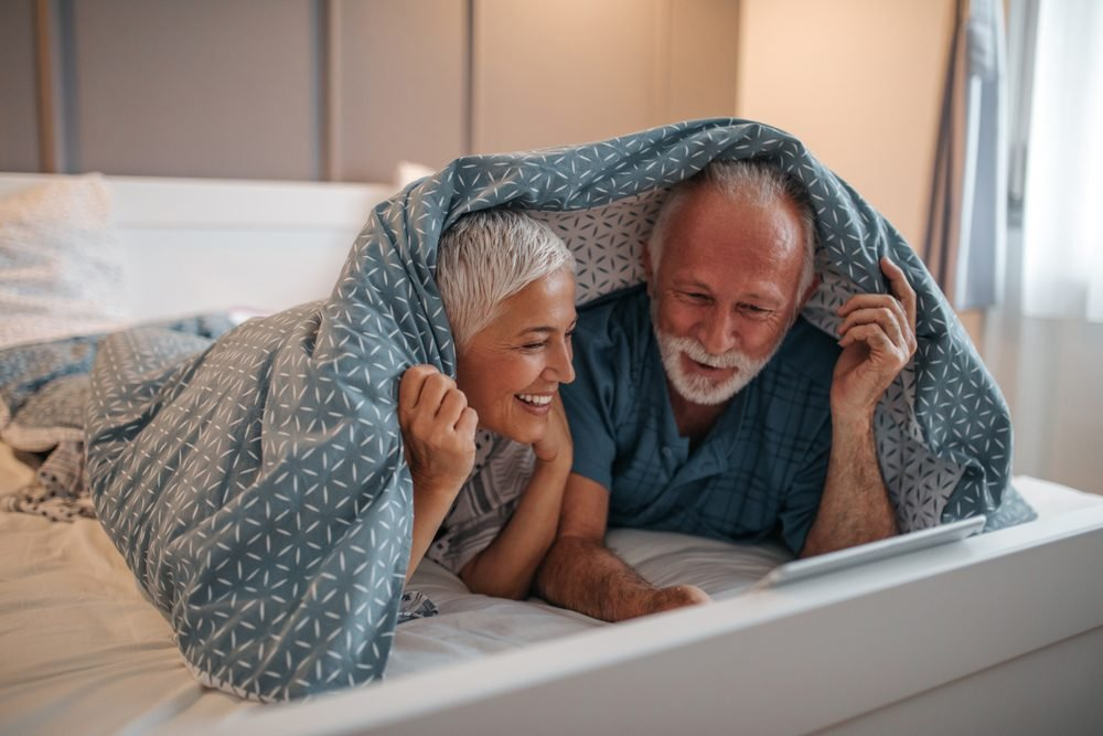 Senior couple using tablet in bed