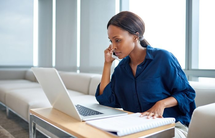 Focused young businesswoman talking on a cellphone and working on a laptop while sitting at a table in a modern office