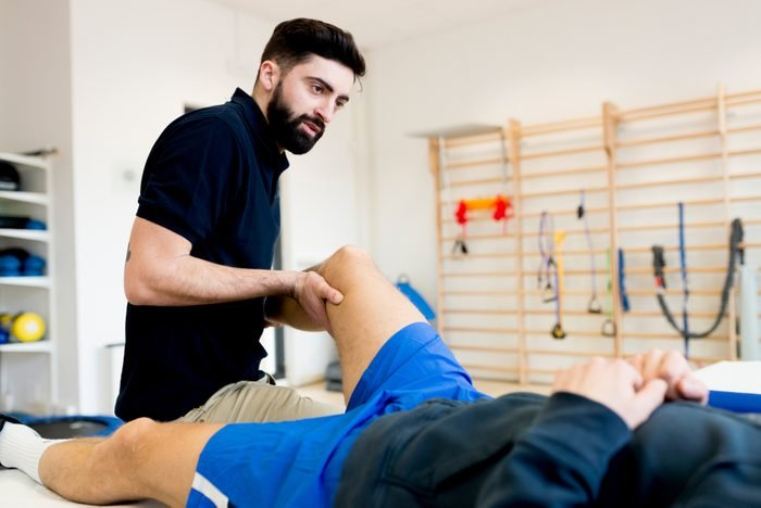 Male therapist treating knee of sporty patient