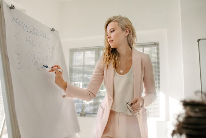 Female manager makes a presentation to colleagues in boardroom. Woman writing on flip chart board during finance meeting in office.