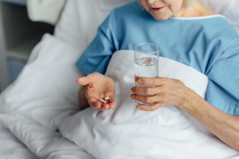 cropped view of senior woman lying in bed and holding pills with glass of water in hospital
