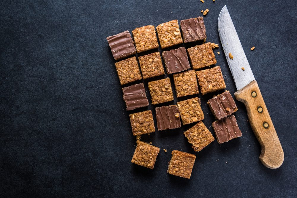 Healthy diet snack, oat flap jack brownie bar. View from overhead on dark slate.