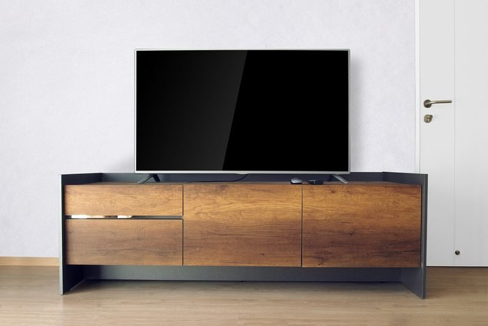Led TV on TV stand in empty room with white concrete wall. decorate in loft style.
