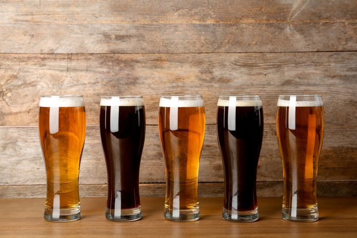 Glasses with beer on table against wooden background