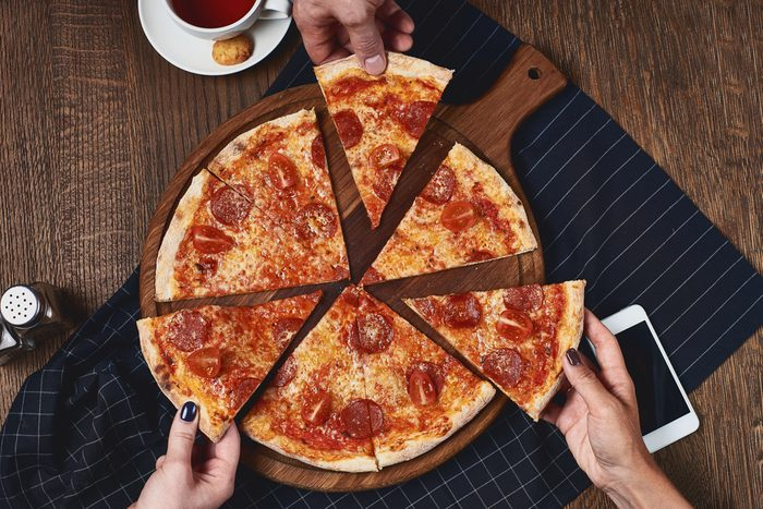 Flatlay. Close-up of people hands taking slices of pepperoni pizza from wooden board. Table served with black textile napkin. Smartphone on table. People eat fast food in cafe.