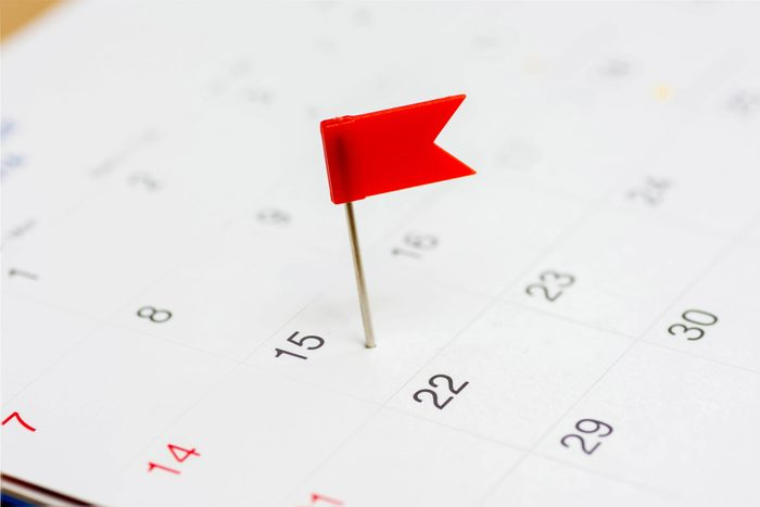 Red color flag pin thumbtack a date on calendar or planner.Tax Day falls on April 15 each year.(selective focus)