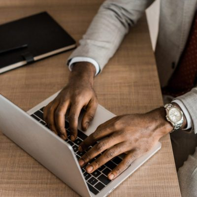partial view of african american businessman typing on laptop