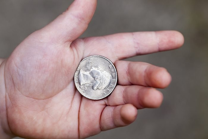 lying in the hand of the child's American coin in a quarter. Photo closeup with a small depth of field.