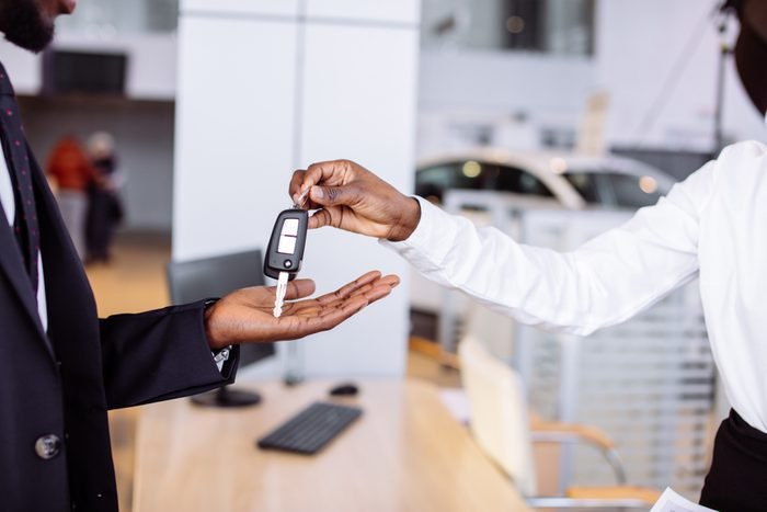 Young car african female salesman giving a key from the new car to the beautiful young african couple owners