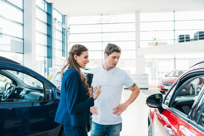 Sales manager describing car to customer in showroom