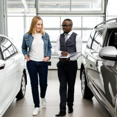 Sales Manager shows the woman new cars in the showroom