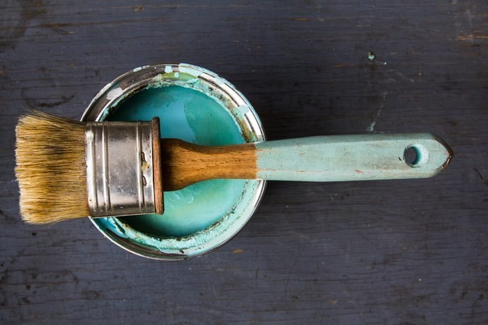 one brush lies on the bank of paint turquoise color on gray wooden background