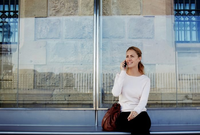 Young beautiful woman talking on mobile phone while waiting public transportation at urban setting station, smiling female having pleasant conversation on cell telephone while sitting on a bus stop
