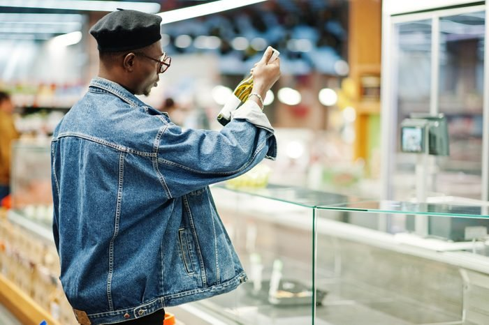 Stylish casual african american man at jeans jacket and black beret holding basket and looking on bottle of wine, shopping at supermarket.