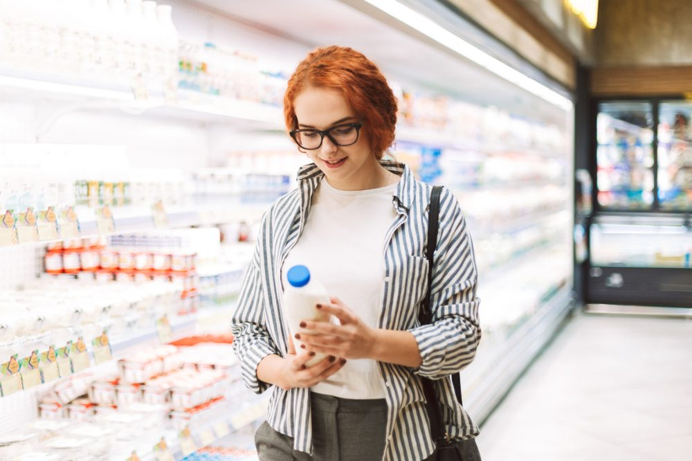Pretty smiling girl in eyeglasses and striped shirt dreamily looking on bottle of milk in hands in modern supermarket