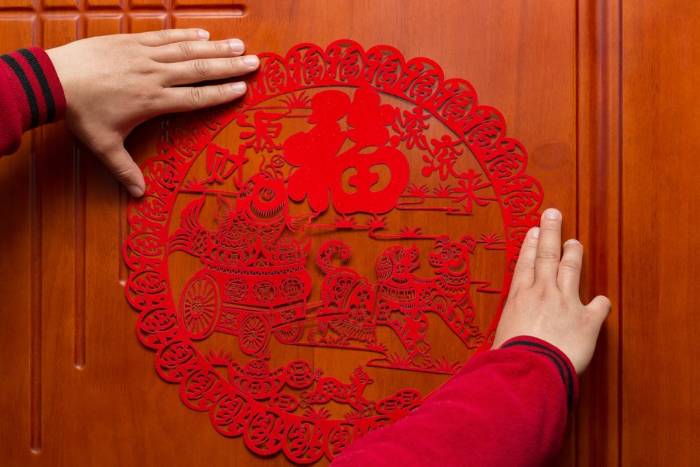 man sticking a Chinese New Year of the Dog 2018 to a door the Chinese means fortune and earn lots of money