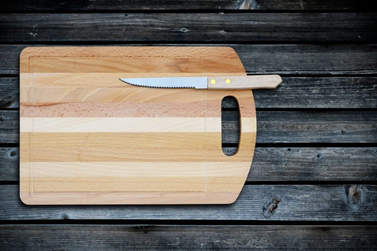 Empty bamboo cutting board and knife on a old wooden table for product display.Top view