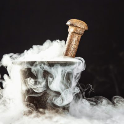Old witcher cauldron illed with magic potion and deep smoke around at black background.