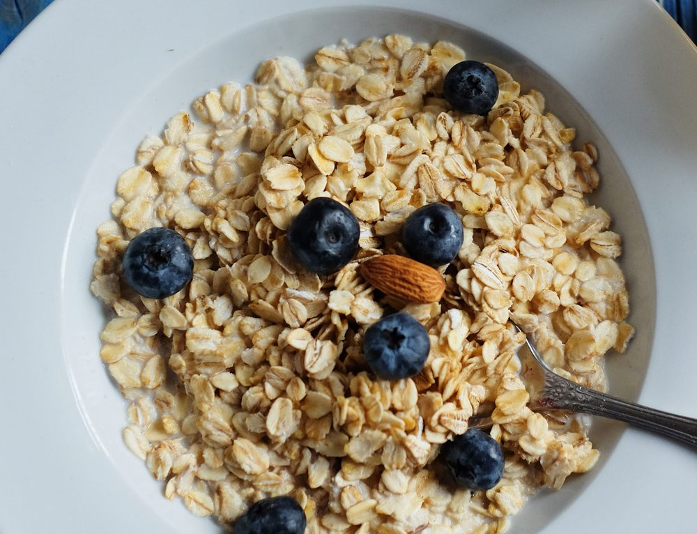 Breakfast with oatmeal and orange juice on blue wooden background