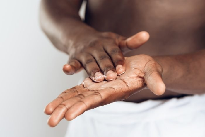African American man smears hands by moisturizing cream. Hand care. Male beauty concept. Isolated on white background.
