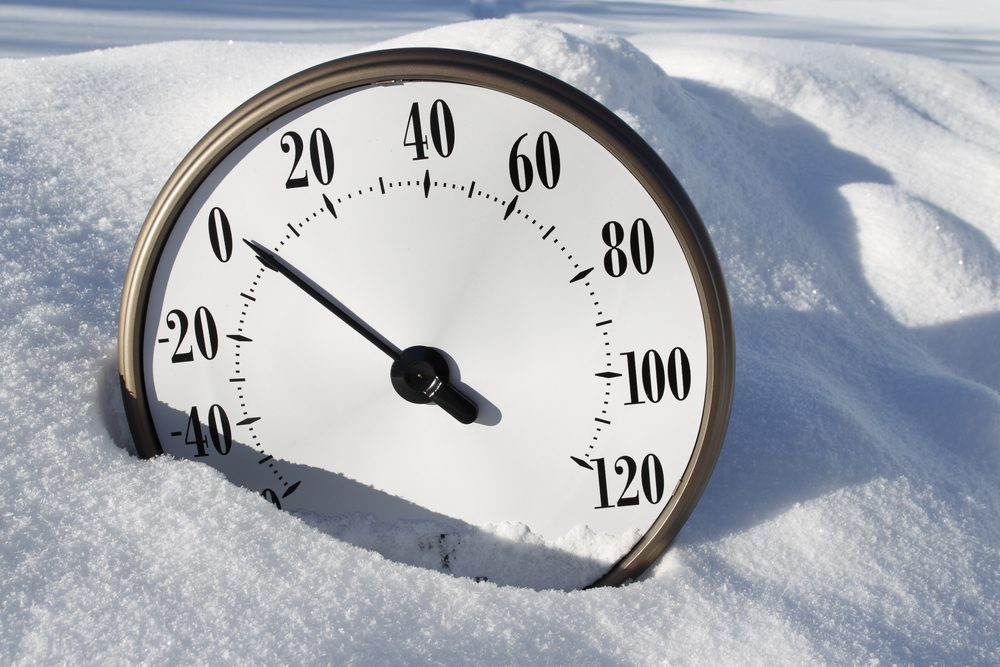A temperature gauge in the snow reading around 0 fahrenheit.
