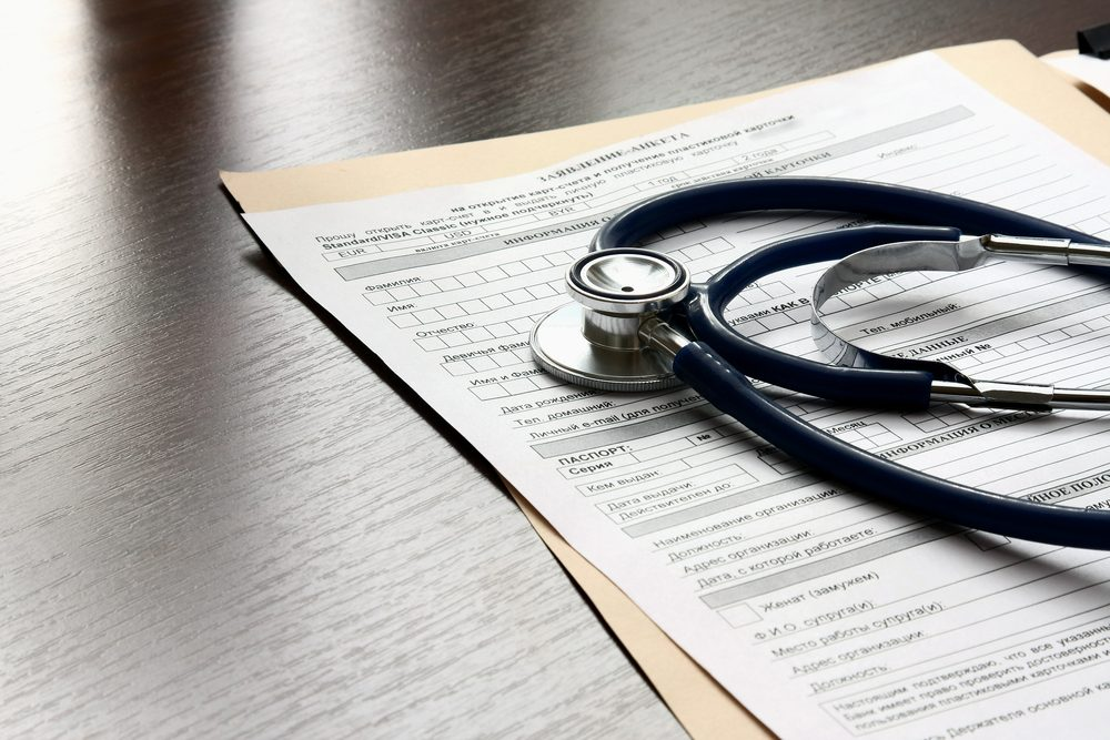 Stethoscope on medical billing statement on table, all text is anonymous