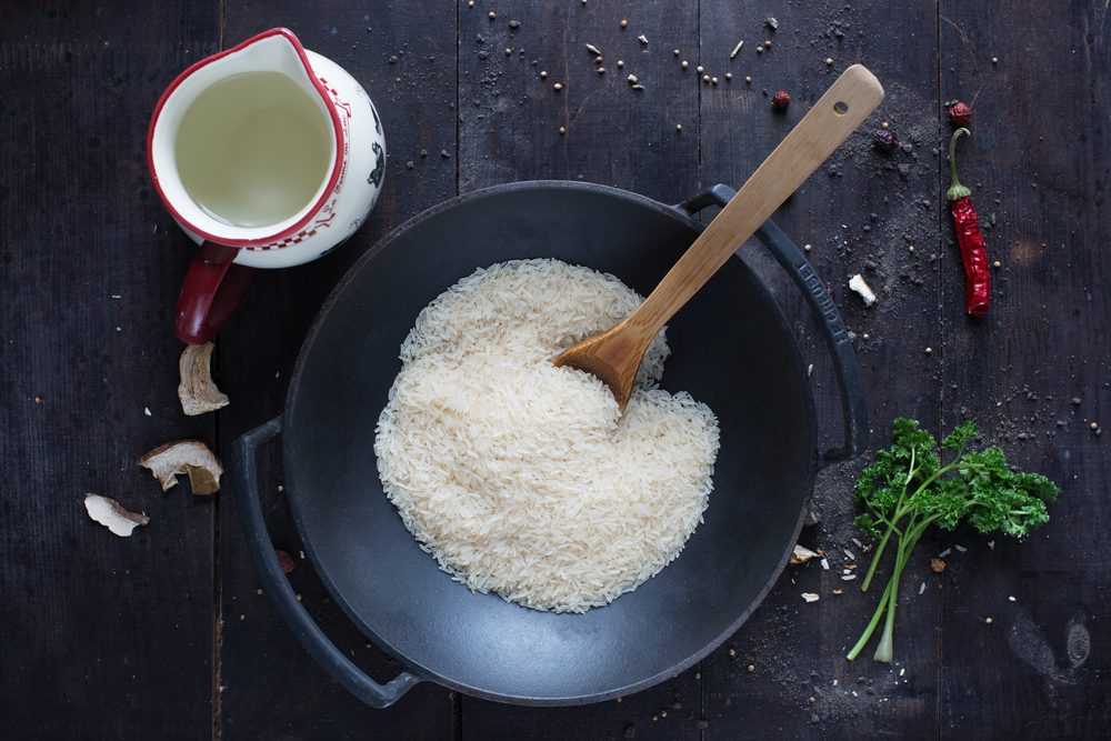 rice in a frying pan with parsley , pepper and water on the dark background