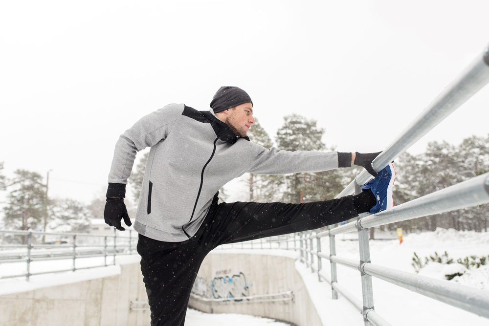 fitness, sport, people, exercising and healthy lifestyle concept - young man stretching leg and warming up at fence in winter