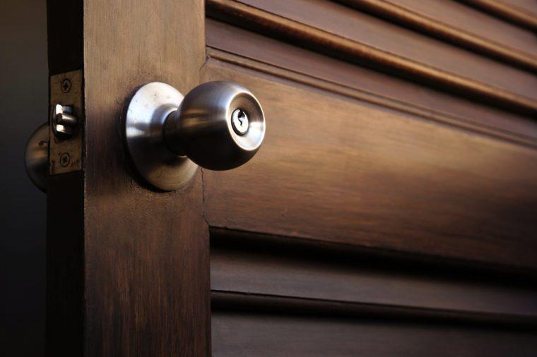 wooden door with grill, stainless door knob or handle on wooden door in beautiful lighting