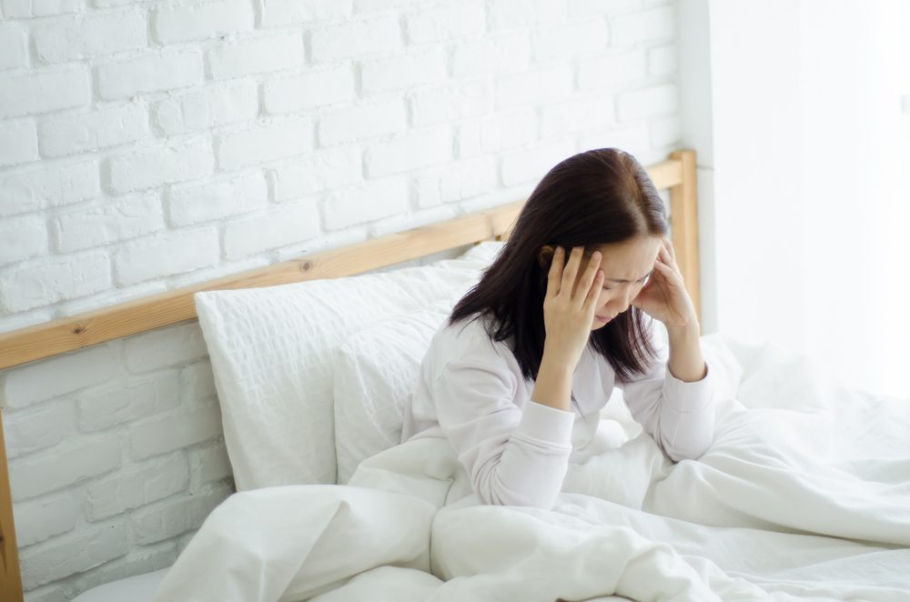 Asian women are headache severely.Lady wake up in the morning with migraine.Insomnia results in headaches when awakened.Young girl sitting on a stressed bed. In her bedroom.She was sick.