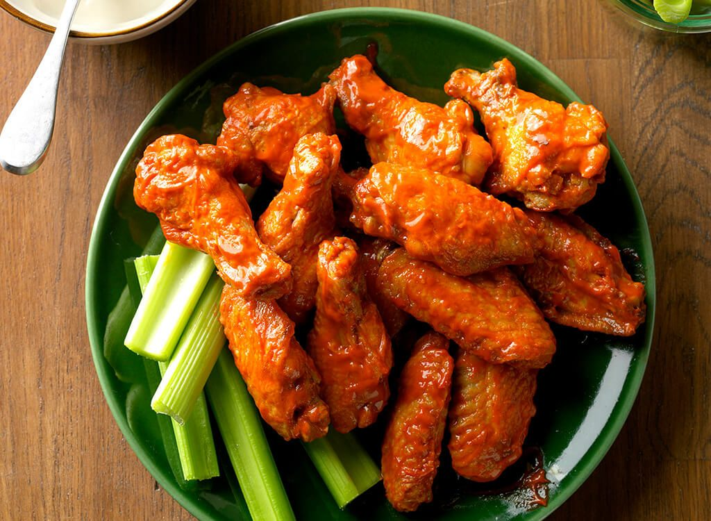 Buffalo wings covered with sauce next to celery