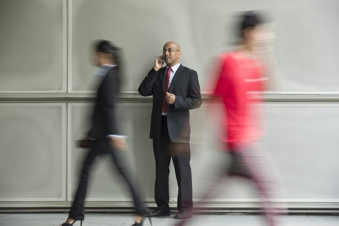 Indian Business man using a Cell Phone with Motion Blurred People walking past.