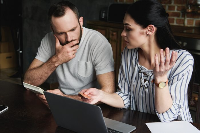 stressed young couple with laptop and calculator counting credit dept