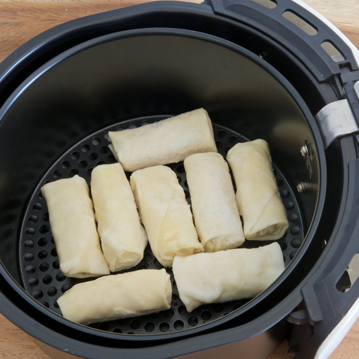 Electric fryer with basket of frozen spring rolls