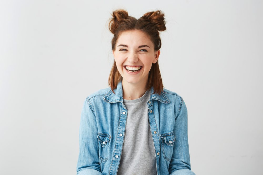 Funny young happy cheerful girl with two buns laughing smiling over white background.
