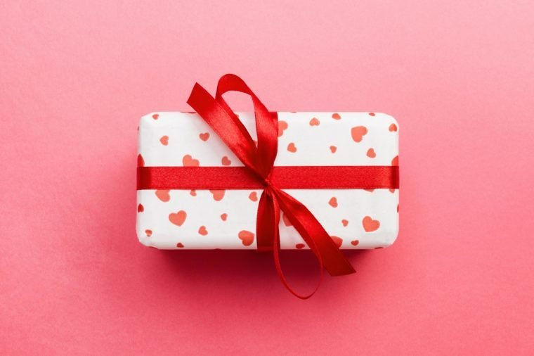gift wrapped in white wrapping paper with red hearts; red ribbon bow; on pink background