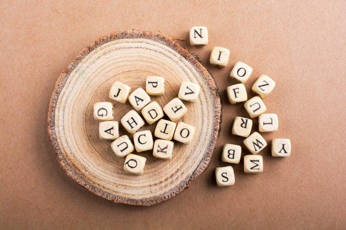 letter tiles on wood slide; brown paper background